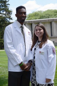 PA students Ken Watson and Emily Reynolds in their white coats.