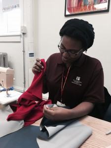 PhilaU student Antonia Robinson '17 assists with sewing  scarves with a hidden pocket for homeless teens.