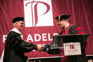 "PhilaU President Stephen Spinelli Jr. congratulates George T. Downs III '63, who received the degree of Doctor of Humane Letters for being the ""epitome of an actively engaged alumnus."""