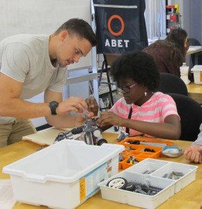 Engineering student Brandon Smith helps camper Leticia Bonds with her model.
