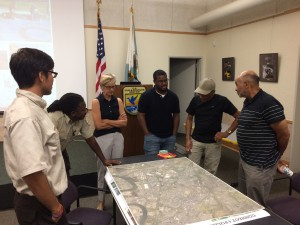 Student Hakeem Wilson '17 (center) presents his pollinator corridor project.