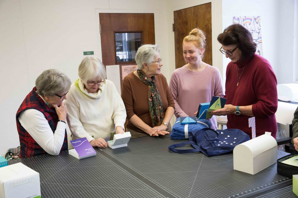 Student Katie Witmer discusses her project with a group of senior citizens who served as testers.
