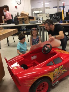 Industrial design senior Alexander Tholl helped Logan and his sister, Ava, apply decals to the car.
